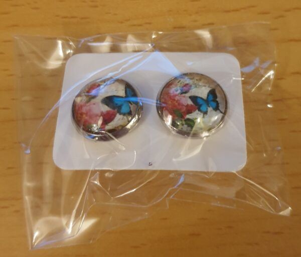 Handmade Butterfly Cabachon Stud Earrings. Beautiful Butterflies adorn this design. The earrings and backs are nickel-free silver-tone. We will however include plastic backs for your choice of use